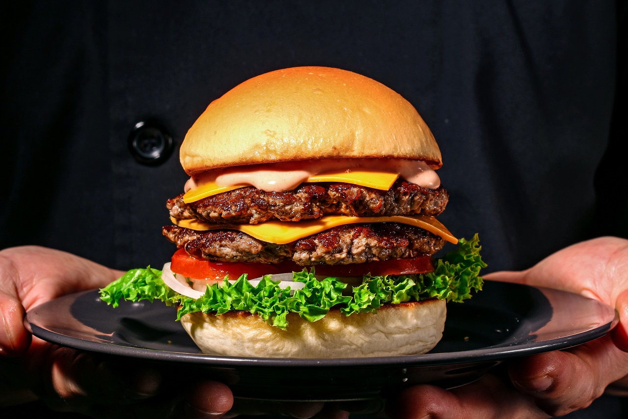 Male-hands-holding-fresh-delicious-beef-burger