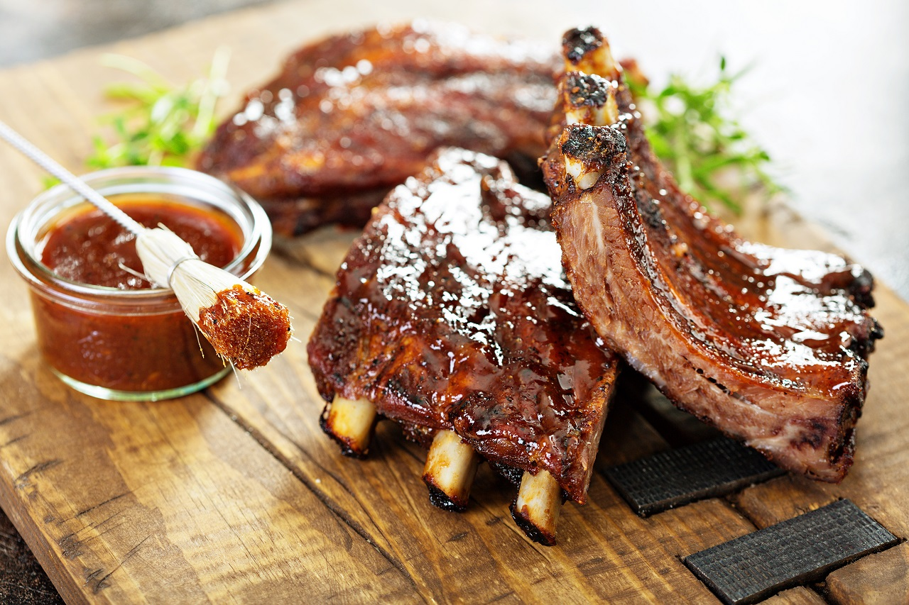 Grilled-and-smoked-ribs-with-barbeque-sauce-on-a-carving-board