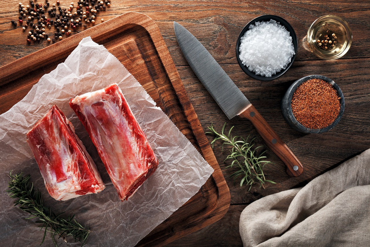 Raw-veal-calf-short-rib-meat-on-white-cooking-paper-and-wooden-cutting-board