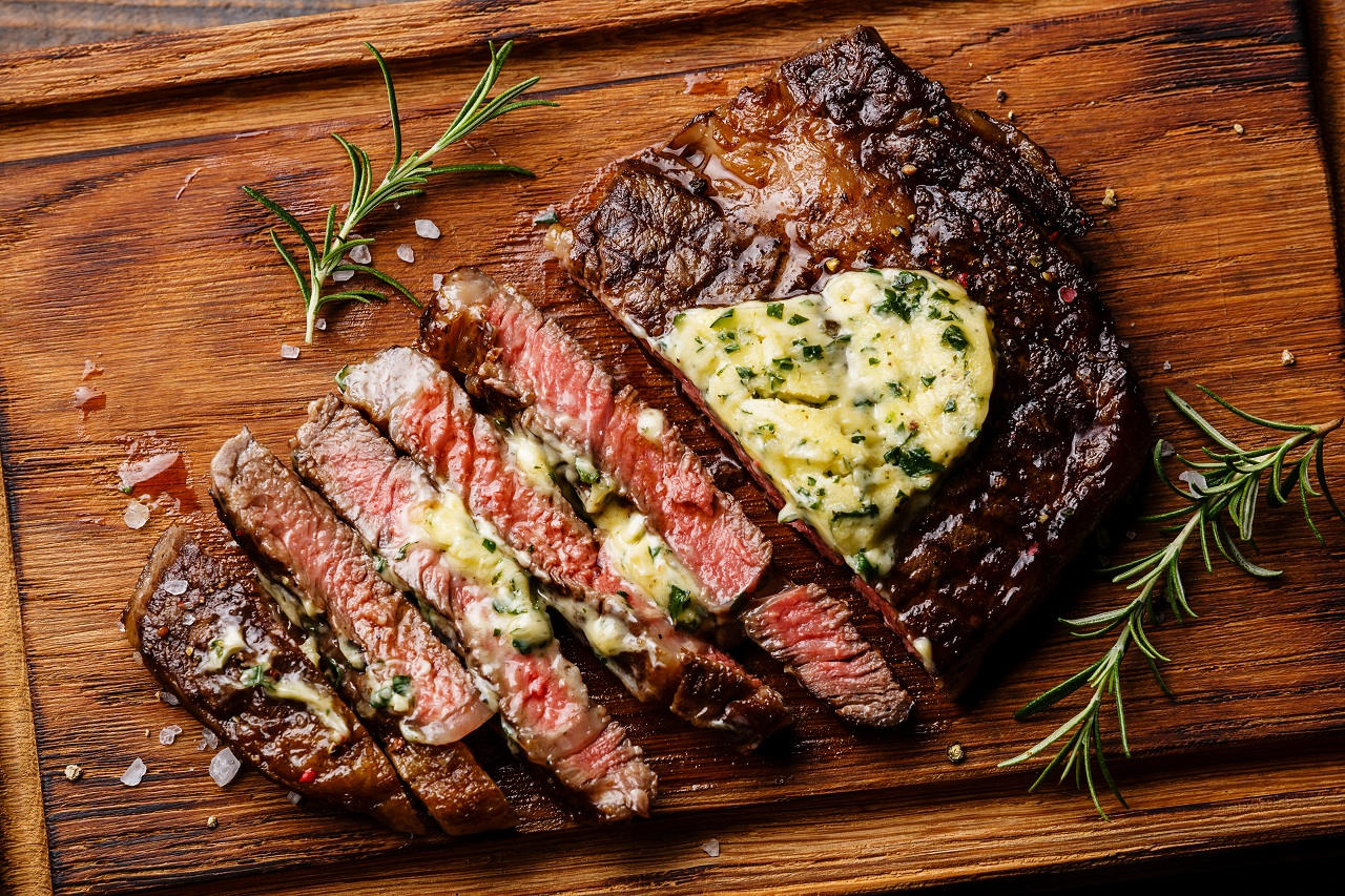 Sliced-grilled-Medium-rare-barbecue-steak-Ribeye-with-herb-butter-on-cutting-board-close-up