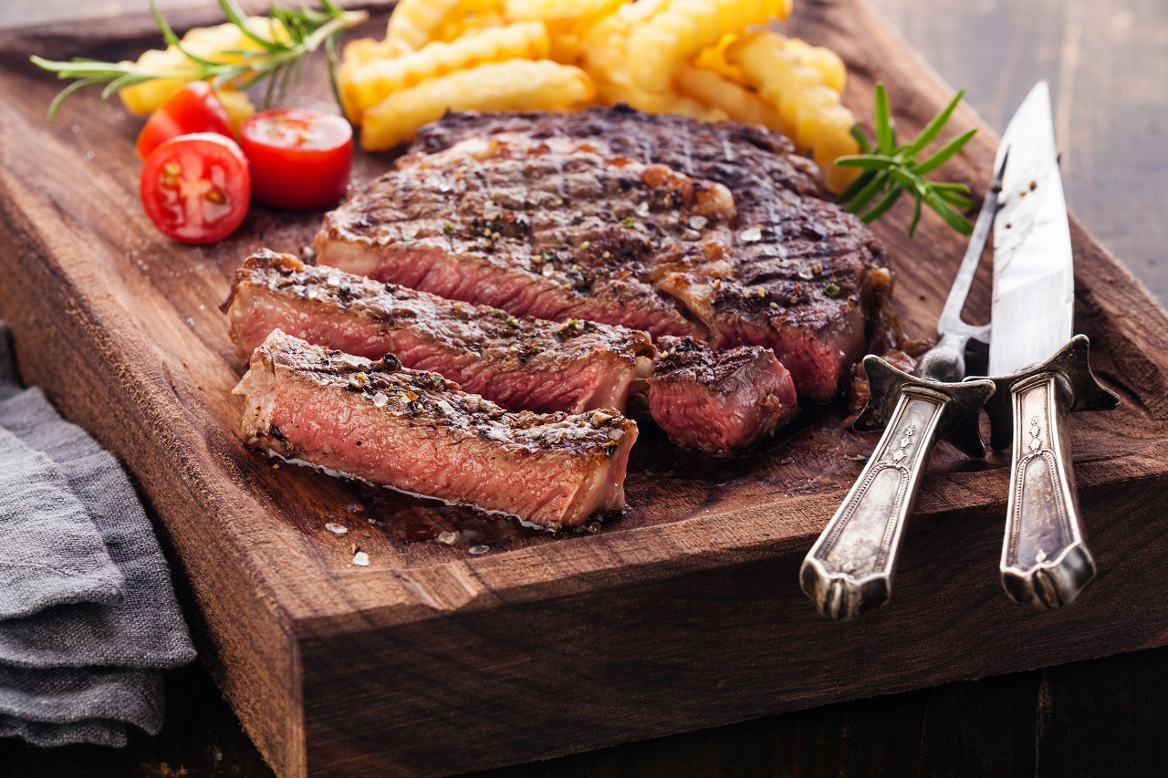 Sliced-medium-rare-grilled-Steak-Ribeye-with-french-fries-on-serving-board-block-on-wooden-background