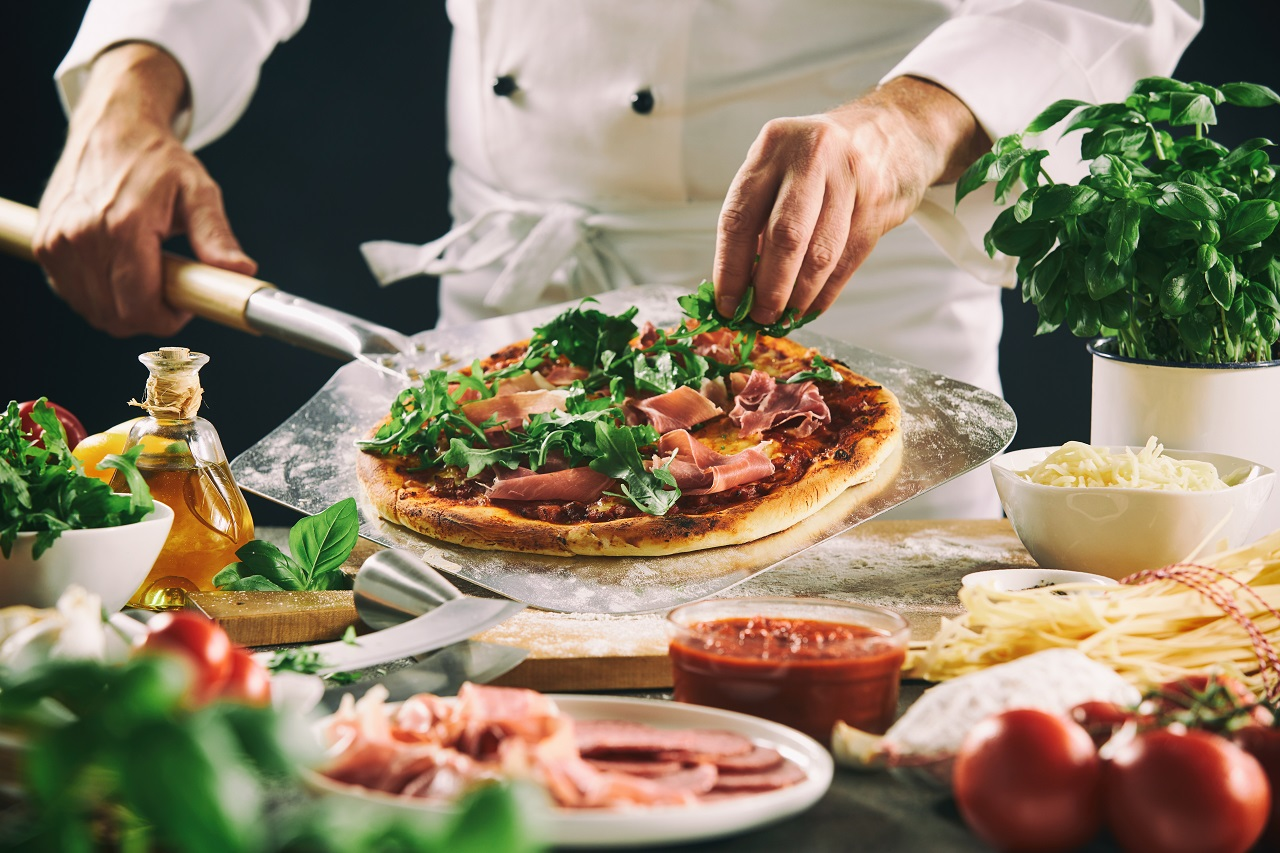 Chef-preparing-an-Italian-pizza-on-a-paddle-placing-assorted-meat-cheese-and-herb-toppings-on-the-pastry-base-in-a-close-up-on-his-hands