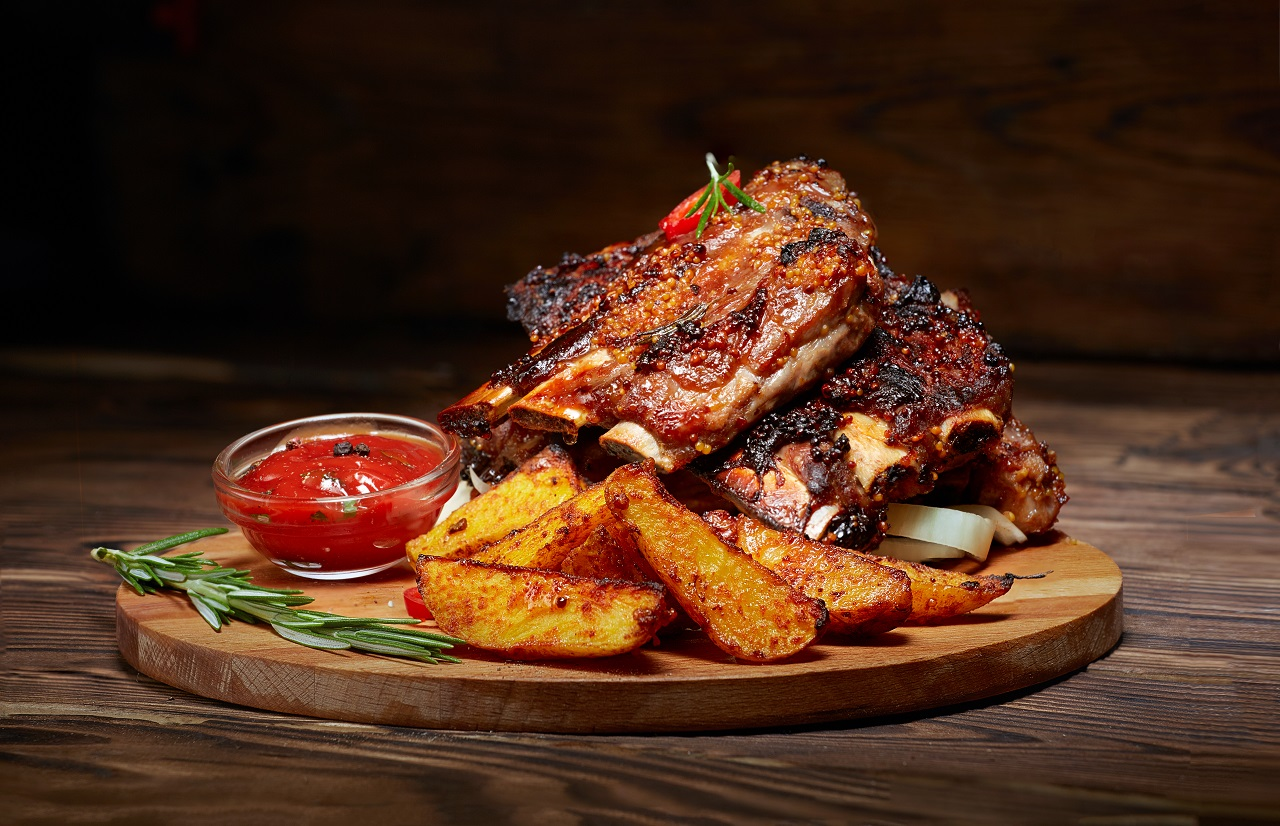 Fried-ribs-with-rosemary-potatoes-rustic-onion-sauce-on-wooden-round-Board
