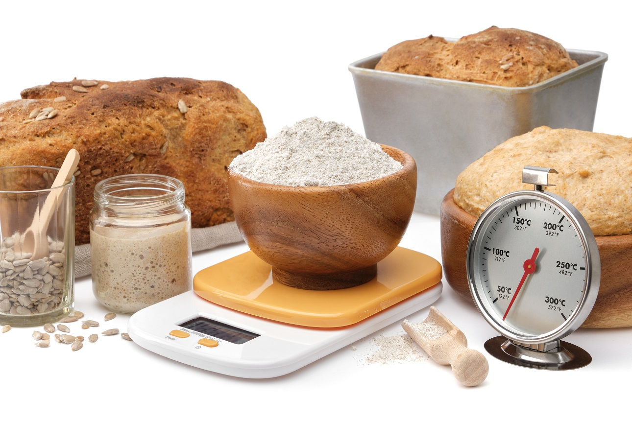 Homemade-sourdough-bread-natural-leaven-for-bread-in-a-glass-jar-wooden-bowl-of-dough-kitchen-scale-a-bowl-of-flour-and-oven-thermometer-on-white