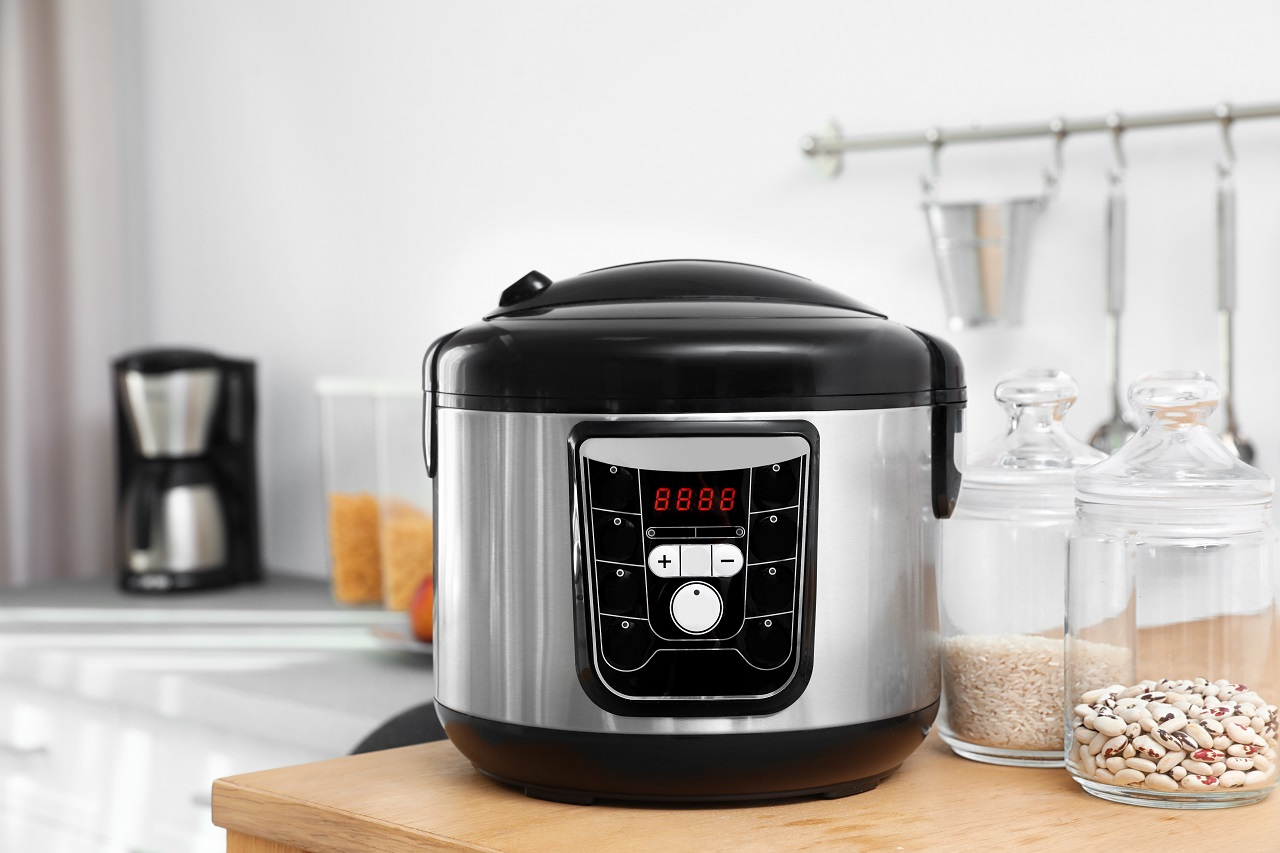 Jars-with-rice-and-beans-near-modern-multi-cooker-on-table-in-kitchen