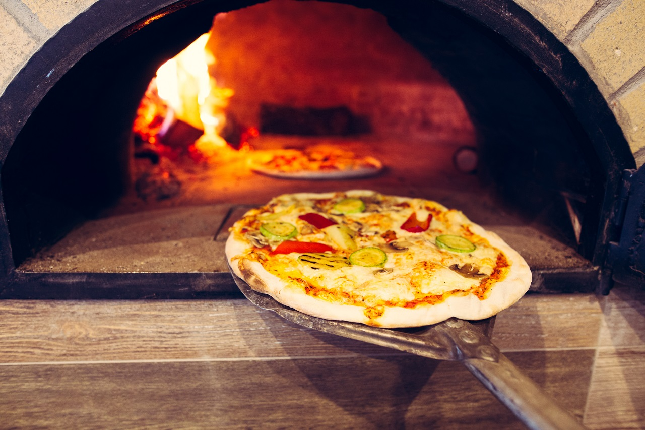 Pizza-cooking-in-a-traditional-brick-wood-oven.Brick-oven-pizza-on-the-wooden-holder-going-to-bake.Colorful-vegetarian-vegetable-pizza-baking