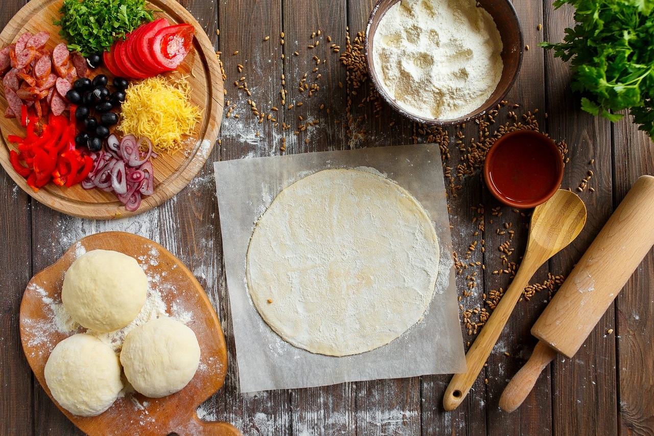 Pizza-dough-with-ingredients-on-wood-table-and-stone-cutting-board-shot-from-above