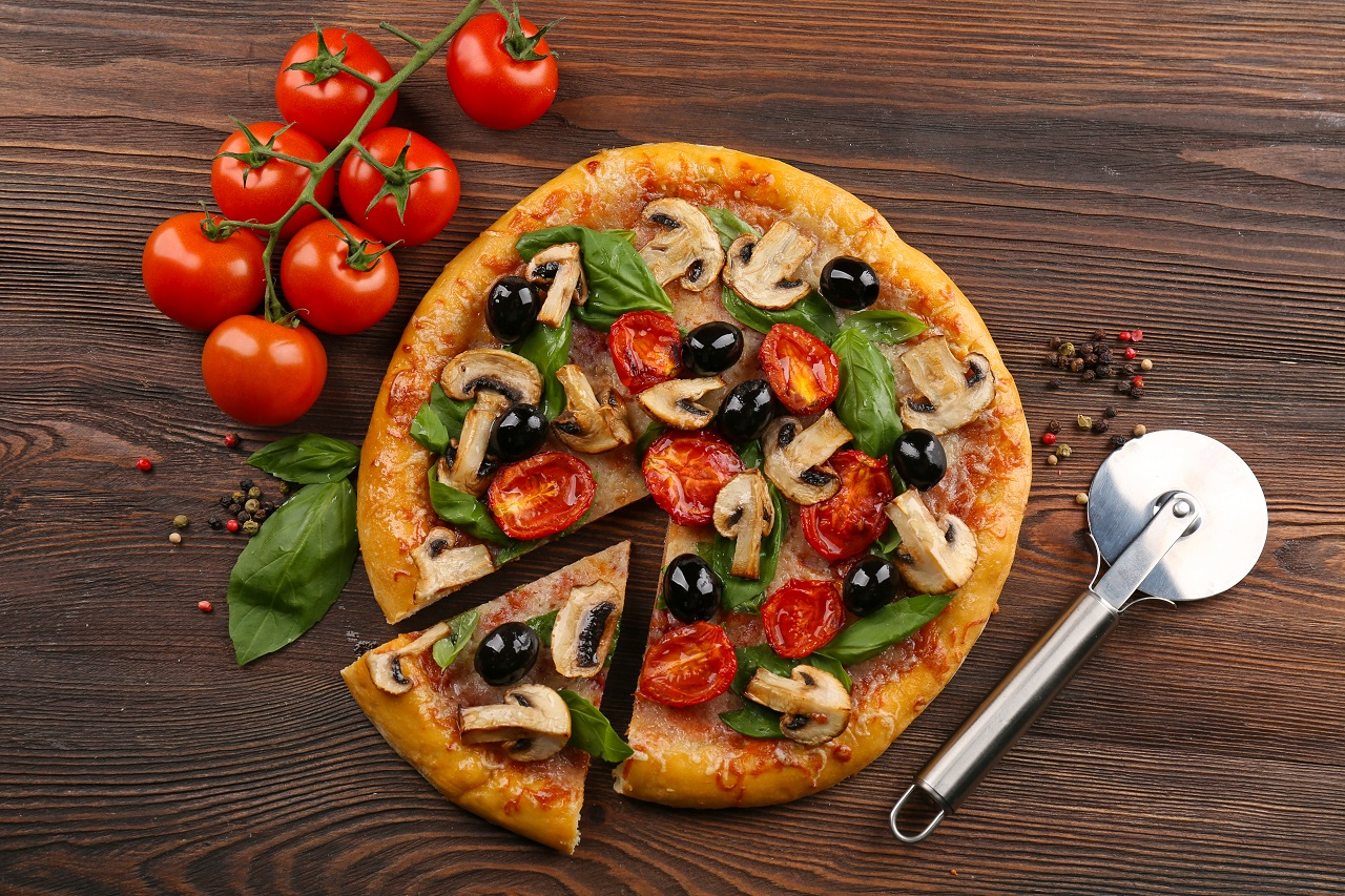 Sliced-delicious-tasty-pizza-with-vegetables-on-wooden-table