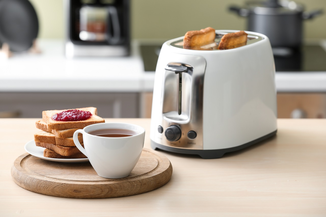 Toaster-with-bread-slices-and-cup-of-coffee-on-table