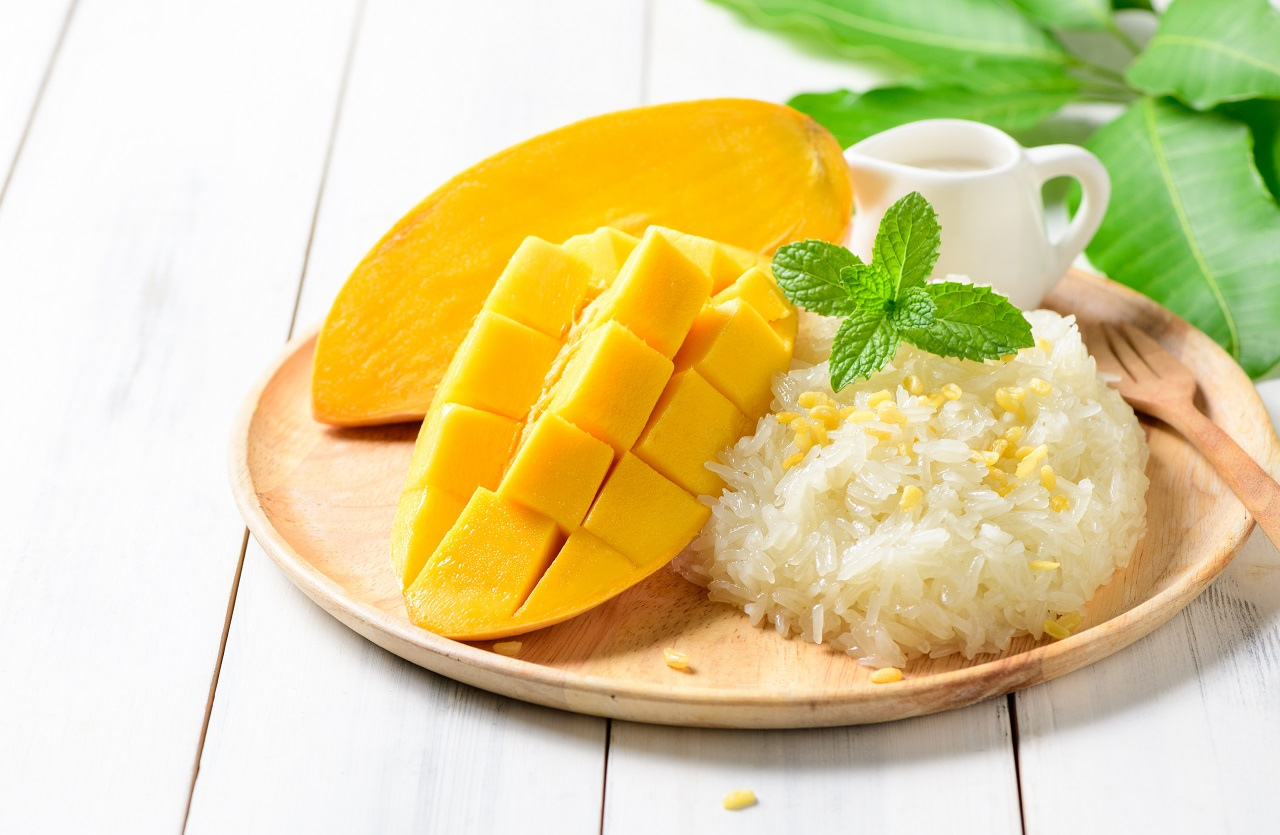 Ripe-mango-and-sticky-rice-with-coconut-milk-on-white-wood-background