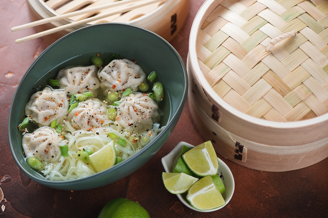 Asian-soup-with-dumplings-and-noodles-served-in-a-green-bowl