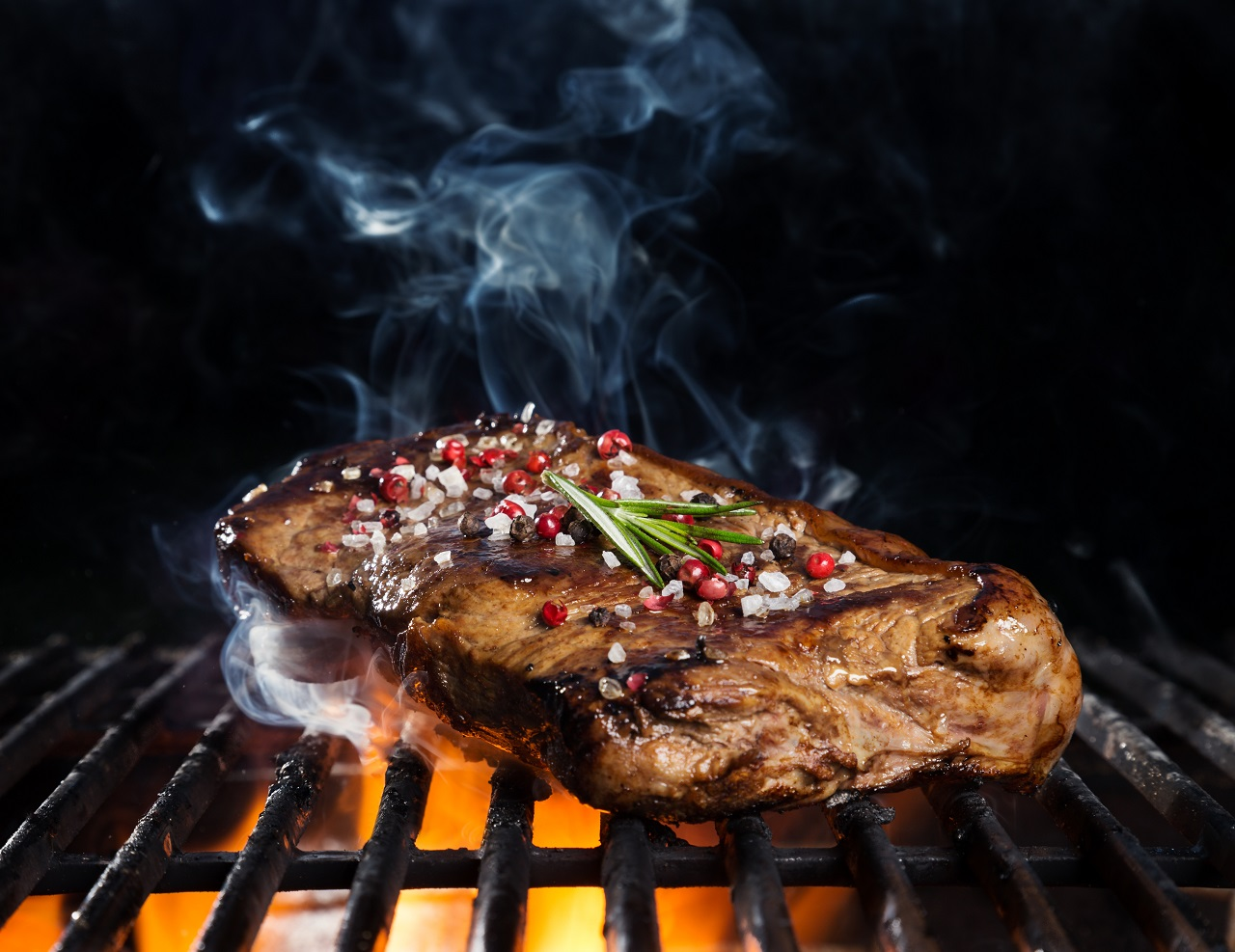 Beef-steak-on-grill-isolated-on-black-background