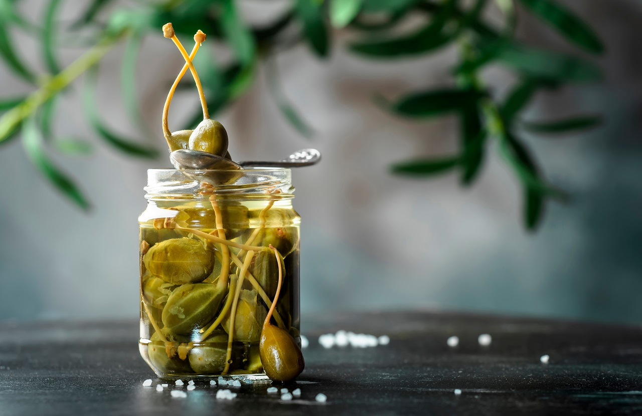 Capers.-Marinated-or-pickled-canned-capers-fruit-close-up-in-glass-jar-on-gray-kitchen-table-background