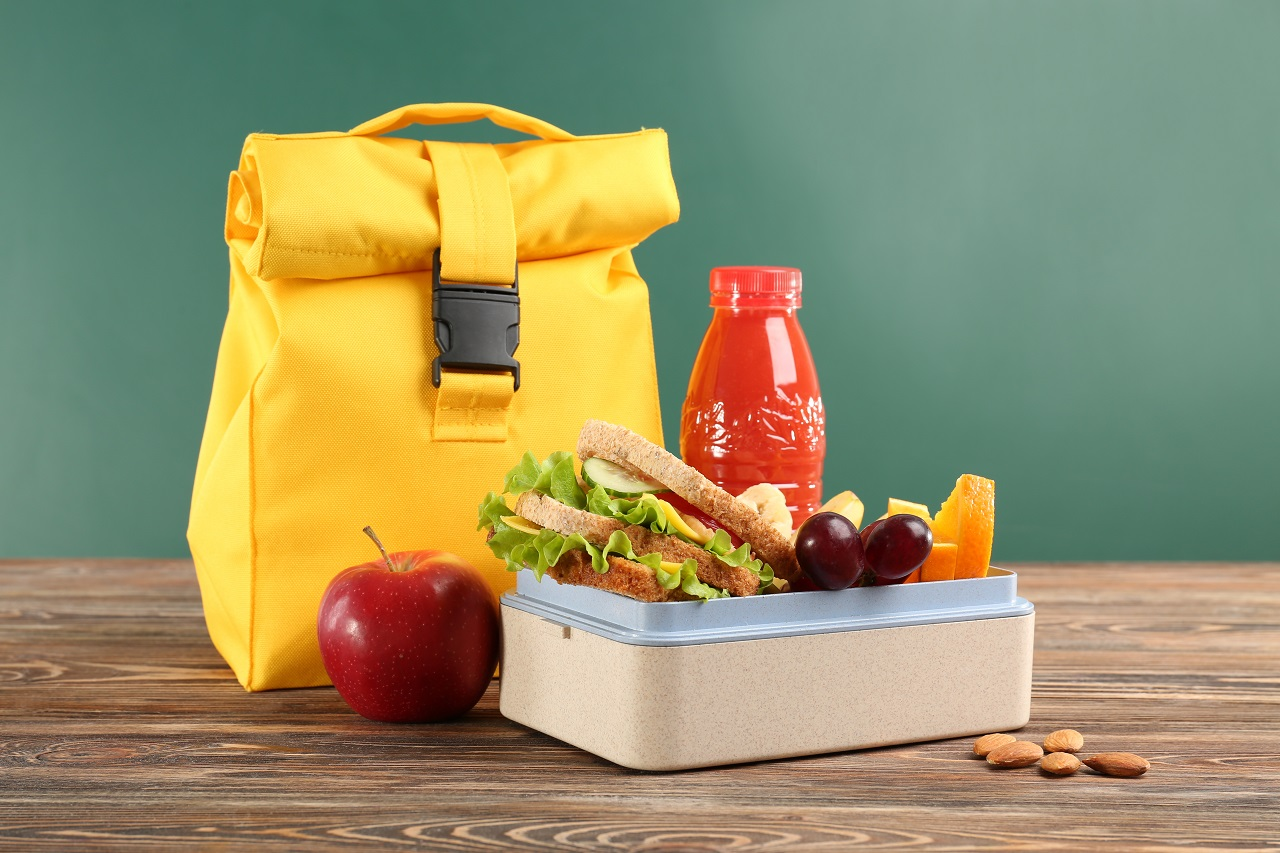 Lunch-box-with-appetizing-food-and-bag-on-wooden-table-against-chalkboard-background