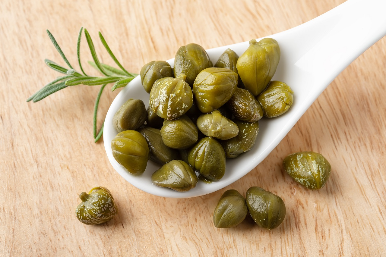 Pickled-capers-in-a-white-porcelain-spoon-on-a-brown-wooden-cutting-board