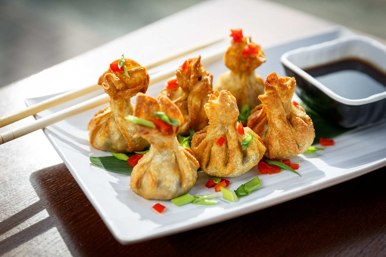 Portion-of-six-fried-wontons-on-a-plate-with-sticks-standing-on-a-table