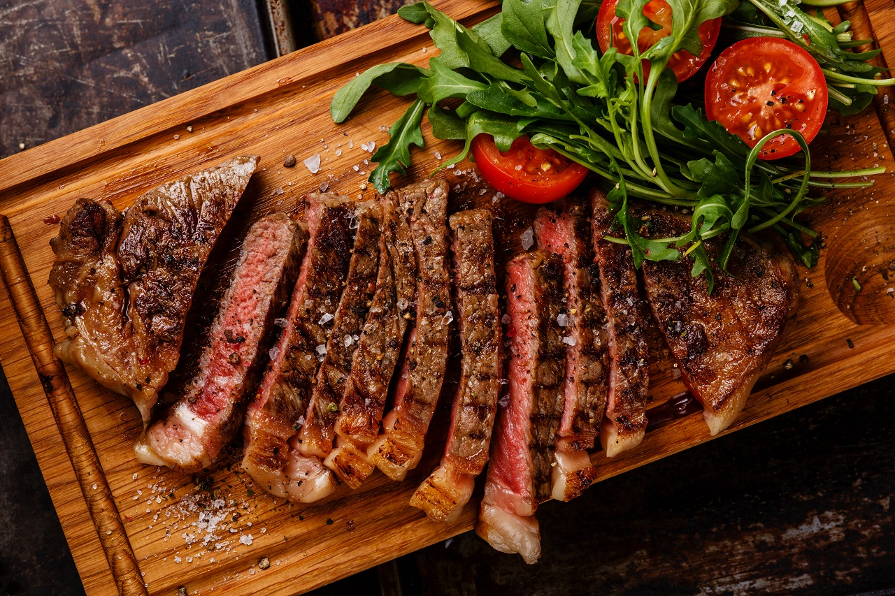 Sliced-grilled-beef-barbecue-Striploin-steak-and-salad-with-tomatoes-and-arugula-on-cutting-board-close-up