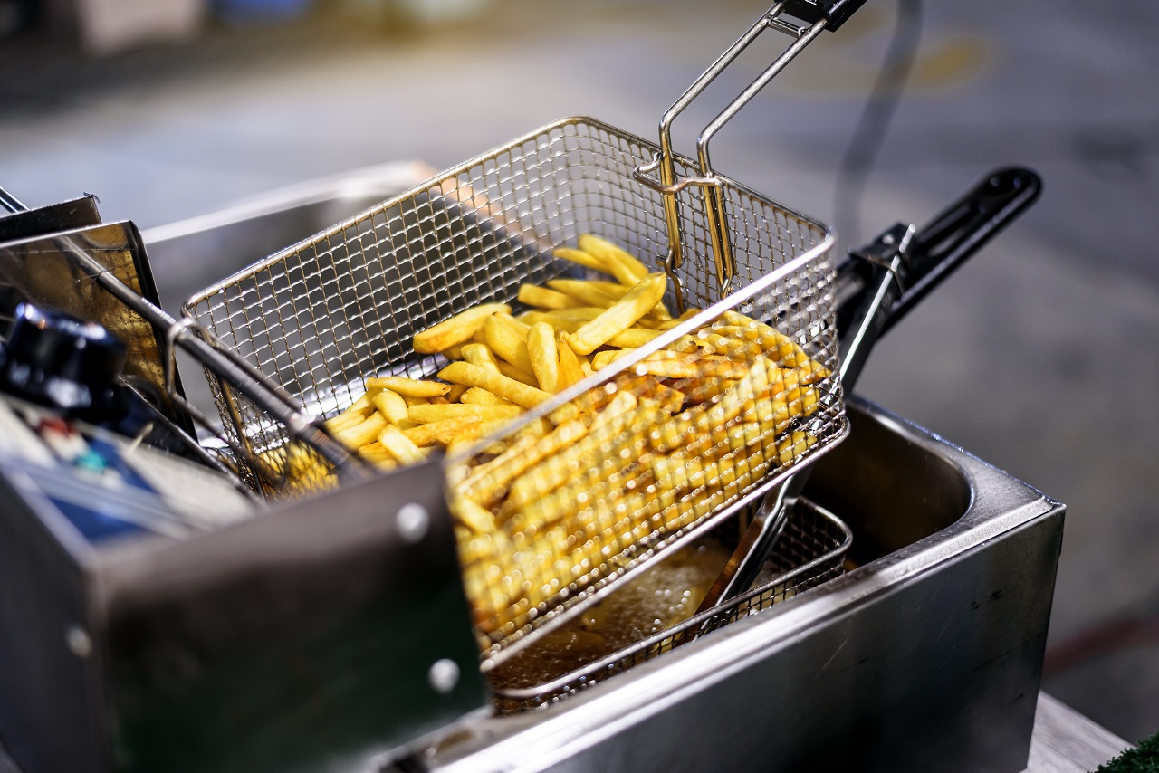 close-up-French-Fries-Potatoes-cooking-in-basket-of-Frying-Machine-deep-fried-in-Hot-Boiling-Oil